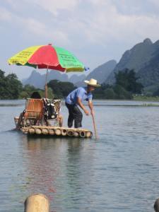 Steering the bamboo raft along the Yulong River in Yangshuo, China