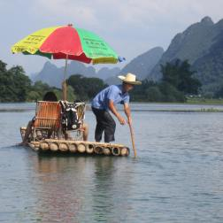 Steering the bamboo raft along the Yulong River in Yangshuo, China