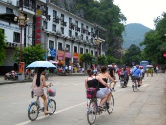 Bikers riding through the town of Yangshuo, China
