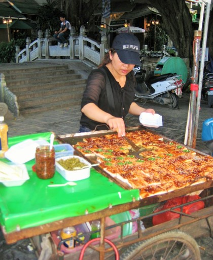 Woman selling mapo tofu, a popular Chinese dish consisting of a popular Chinese dish of tofu in a spicy chili sauce