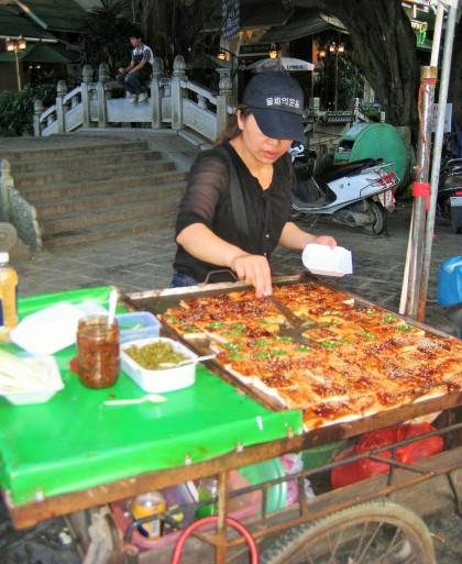 Woman selling mapo tofu, a popular Chinese dish consisting of a popular Chinese dish of tofu in a spicy chili sauce