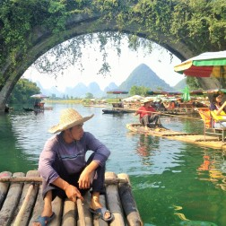 Our guide steering the bamboo raft along the Yulong River in Yangshuo China