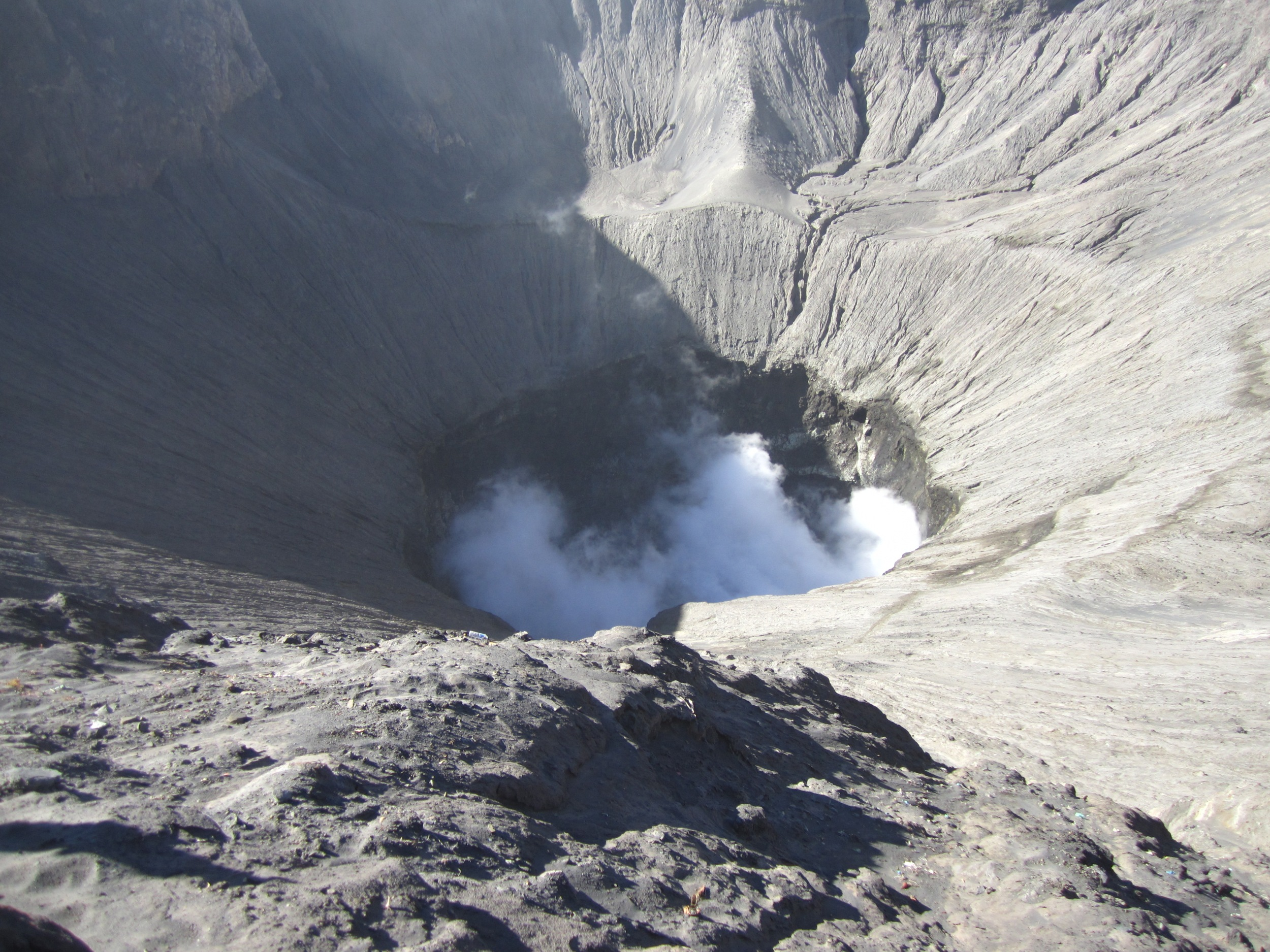 Bromo's massive crater spewing white sulphurous smoke