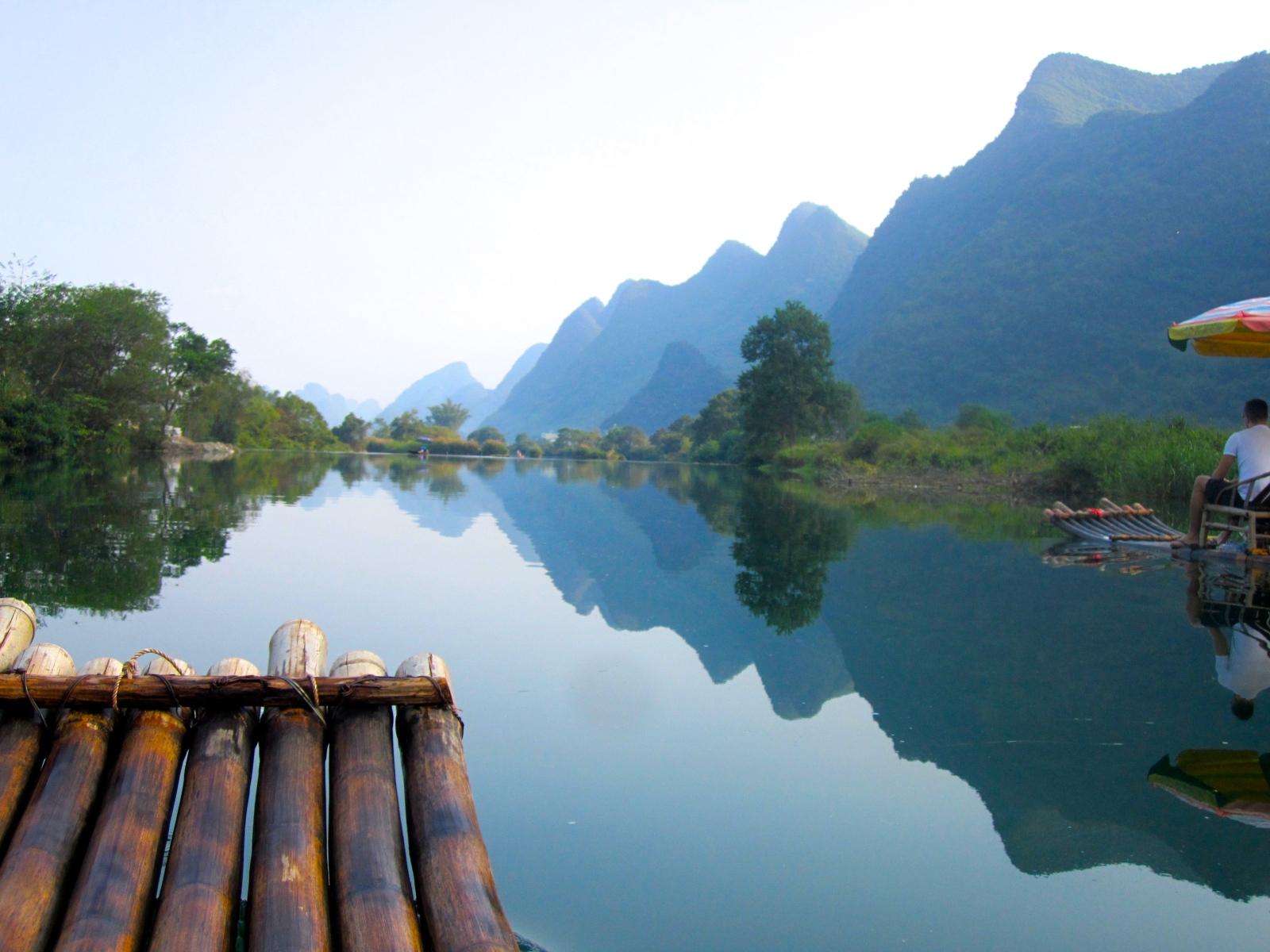 Rafting down the Yulong River among the limestone hills in Yangshuo, China