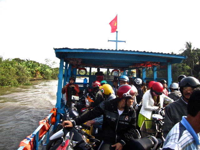 Rustic ferries transporting locals on motorbikes to the other side of the Mekong Delta