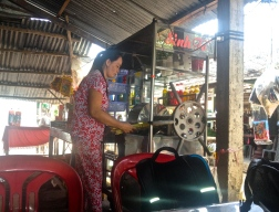 A South Vietnamese woman making sugar cane juice with a manual press