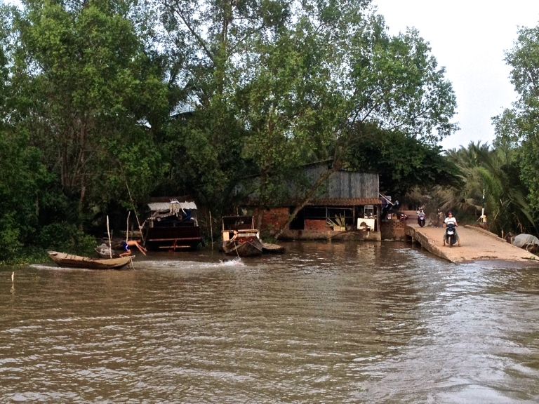 Kids playing in boats and riding motorbike along the Mekong Delta in Southern Vietnam