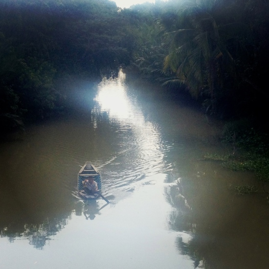 Man paddling his rowboat along the Mekong Delta in South Vietnam