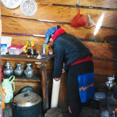A Tibetan woman in Yubeng making Yak butter tea