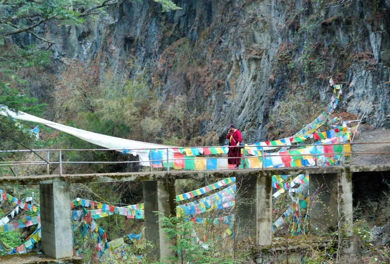 A monk on his cell phone walking across a bridge in Yubeng, China