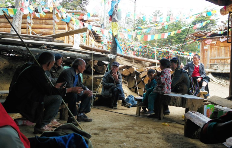 Tibetans enjoying Yak tea and cigarettes at a resting stop on the hike to Yubeng