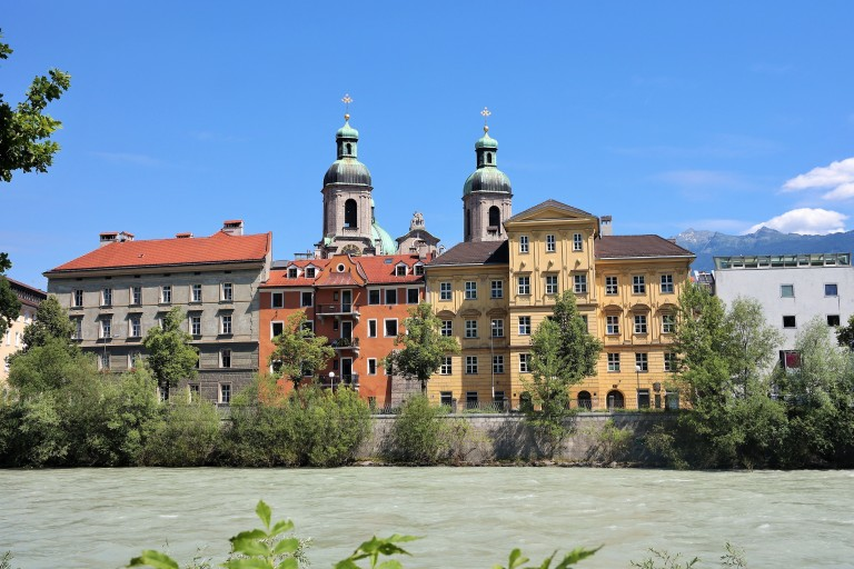 View of the colorful buildings and church along the Inn River in Innsbruck, Austria