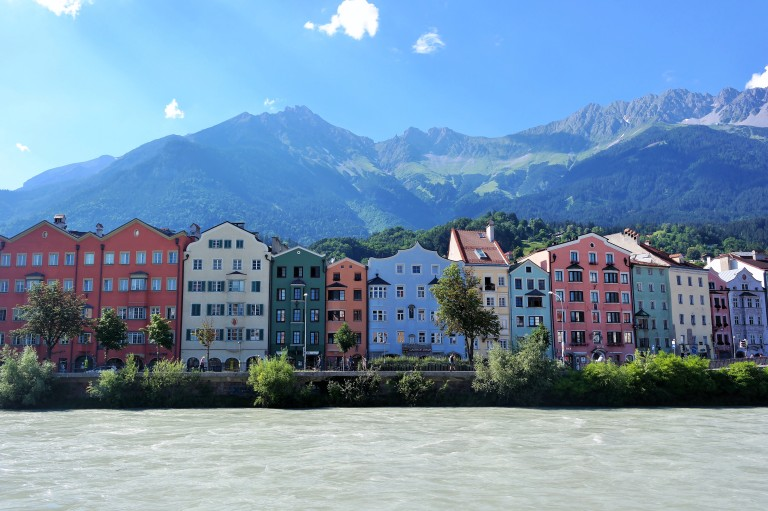 View of colorful homes and buildings along the Inn River in Innsbruck, Austria